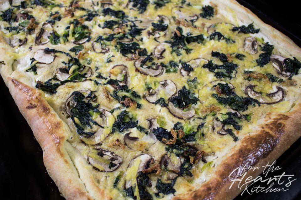 White Pizza mit frischem Spinat, Pilzen, knusprigen gerösteten Knoblauchflocken und veganer Creme Fraiche