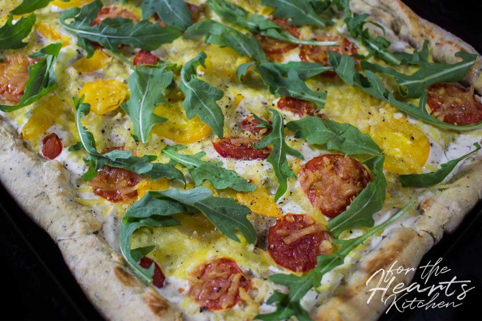 White Pizza mit Knoblauch-Kräuter-Pizzateig, Tomaten, Rucola und einer veganen Creme Fraiche Sauce