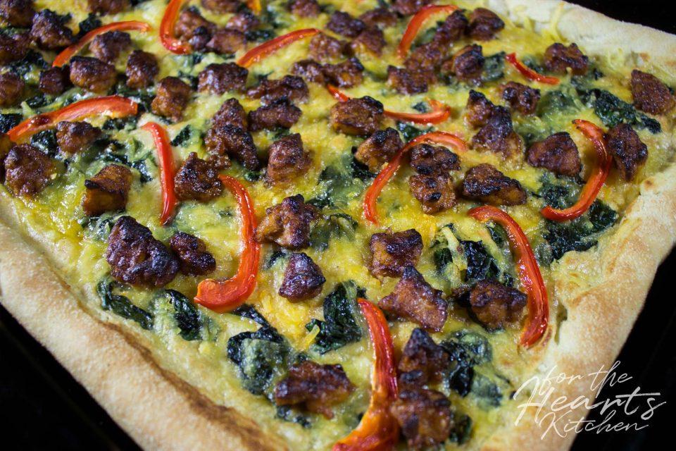 White Pizza mit spicy Buffalo Tempeh, Würzspinat, Paprikastreifen und Cashew Mascarpone